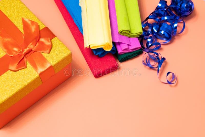Na różowym tle, złoto i czerwień boksujemy z łękiem, pakujący barwiącego panwiowego papier i błękitnego faborek dla wiązać prezen zdjęcia royalty free