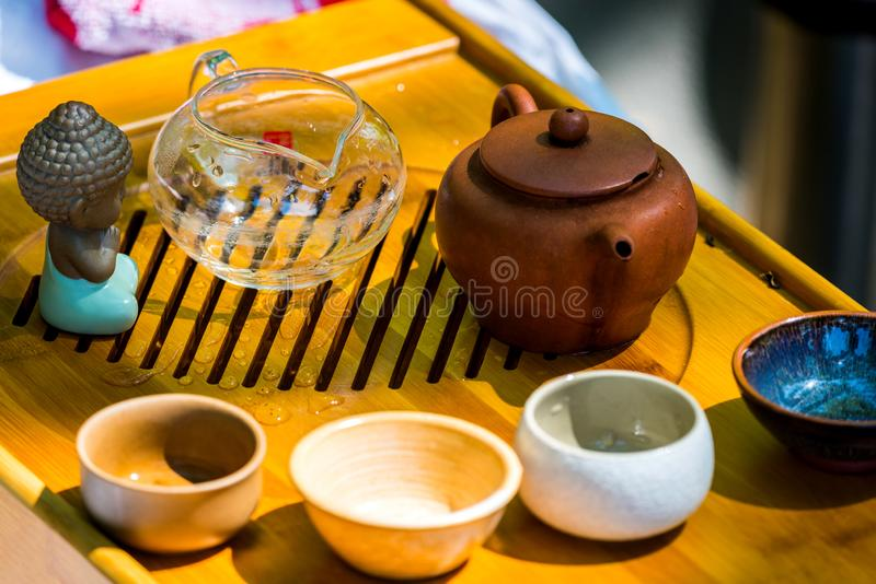 Na stole na drewnianej tacy teapot z herbatą, teapot, filiżanki Mężczyzna, ręki nalewa herbaty obraz royalty free