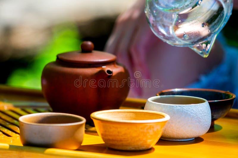 Na stole na drewnianej tacy teapot z herbatą, teapot, filiżanki Mężczyzna, ręki nalewa herbaty fotografia royalty free