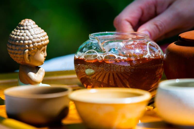Na stole na drewnianej tacy teapot z herbatą, teapot, filiżanki Mężczyzna, ręki nalewa herbaty zdjęcia royalty free