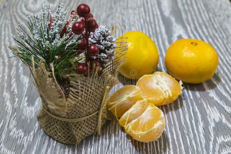 Na stole jest dekoracyjny bukiet jedlinowe gałąź, jagody i rożki, Blisko są tangerines obrazy royalty free