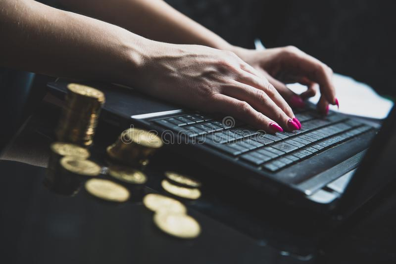 Na stole kłama mnóstwo złociste monety w tle, kobiety pracy na laptopie obrazy royalty free