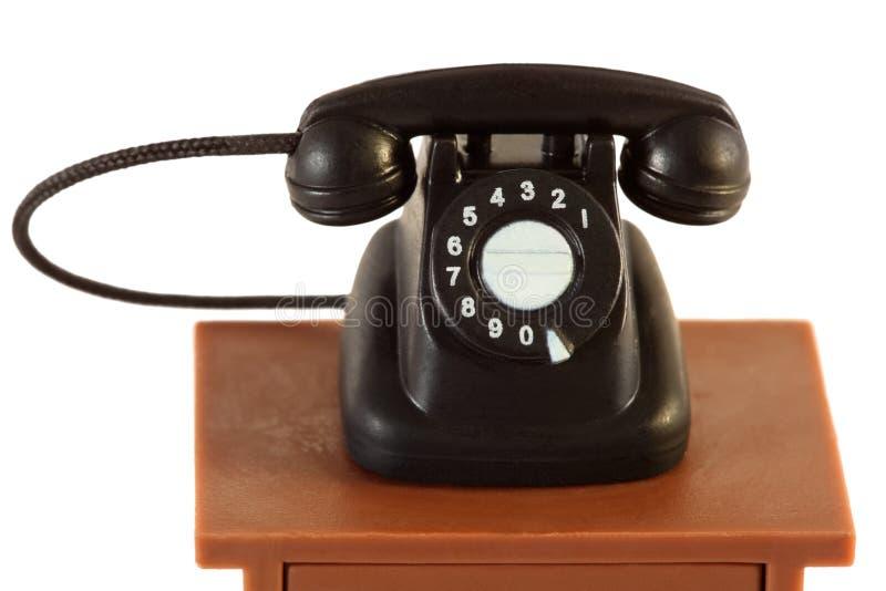 Na stole odizolowywającym mały retro telefon obraz royalty free