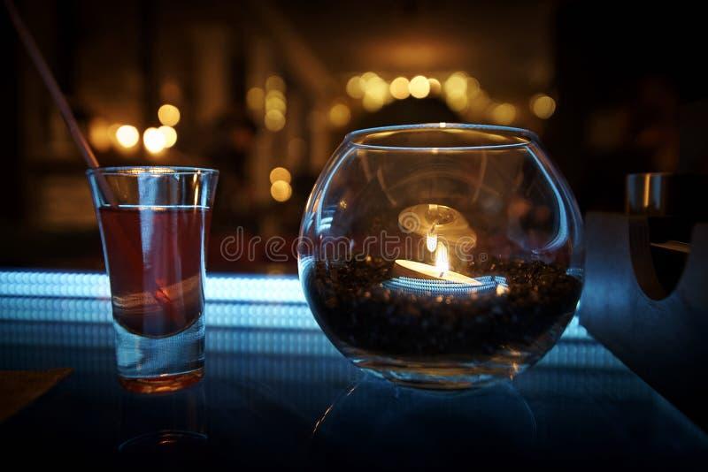 Na stole z błękitem backlight stoi candlestick i koktajl obraz stock