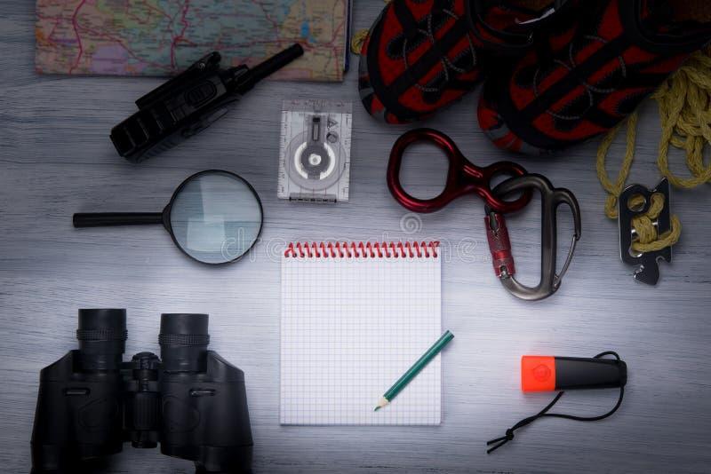 Na szarym tle, jest set podróżników wygodni buty, arkana, carabiners, powiększa - szkło, lornetki, kompas, mapa, walkie zdjęcia royalty free