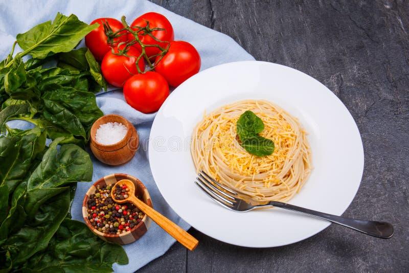 Na tabela é a parcela com massa, tomates, verdes e especiarias imagens de stock royalty free