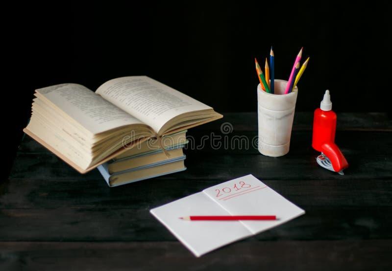 Na tabela colocada um livro, bloco de notas com pena, fotos de stock royalty free