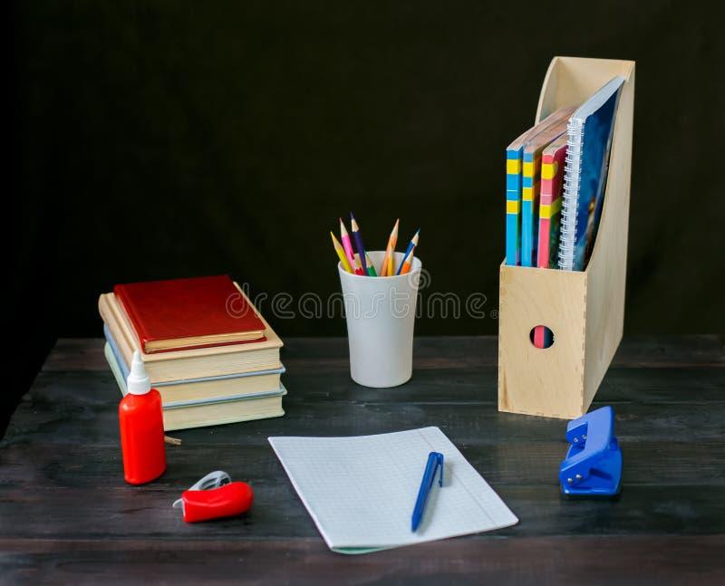 Na tabela colocada um livro, bloco de notas com pena, fotografia de stock royalty free
