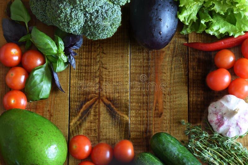 Na tabela de madeira são belamente os vegetais e os frutos: tomates, pepinos, abacates, beringelas, brócolis, tomilho, manjericão fotografia de stock royalty free