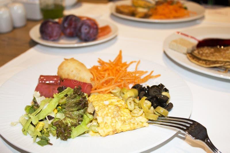 Na tabela em uma omeleta da placa com salsichas e o vegeta cortados imagem de stock