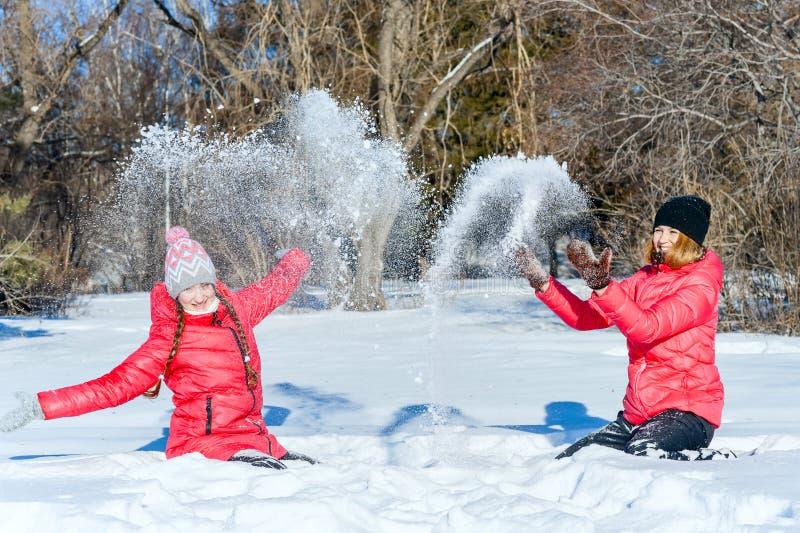 na terenach odkrytych portret Dwa młoda szczęśliwa dziewczyna rzuca up śnieg Showere fotografia stock