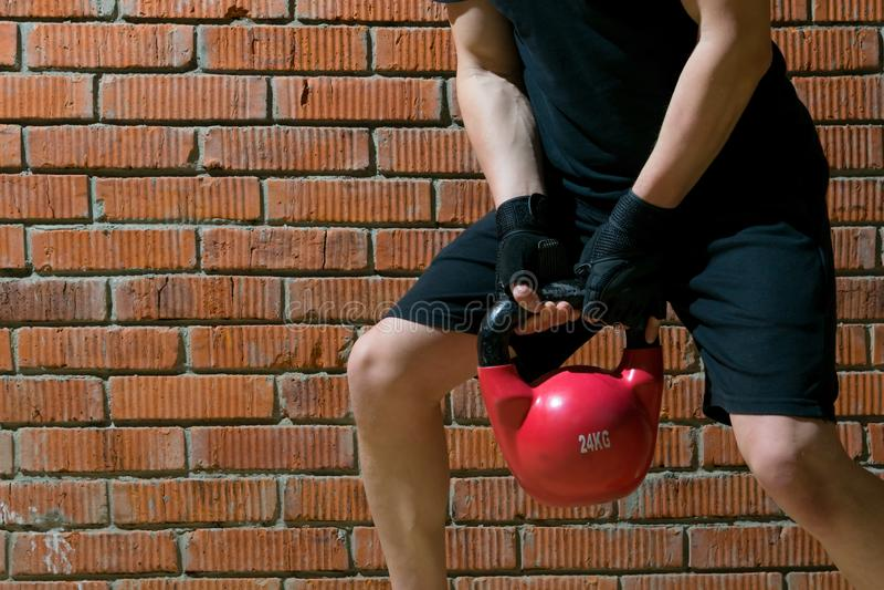 Na tle pomarańczowej cegły, mężczyzna w czarnym mundurze, uprawia sport, podnosi duży czerwony ciężar, zbliża się, jest miejsce obrazy stock