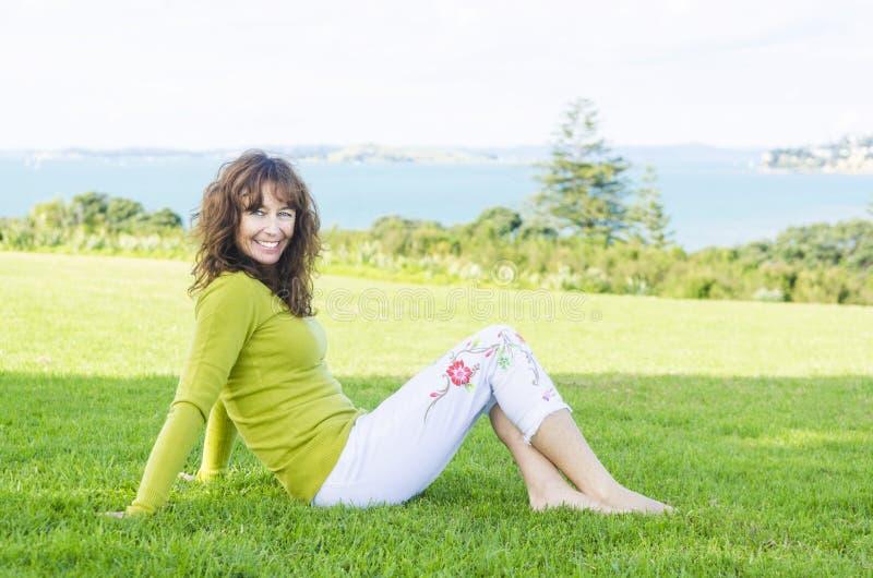 Na trawie kobiety szczęśliwy uśmiechnięty dojrzały obsiadanie zdjęcia stock