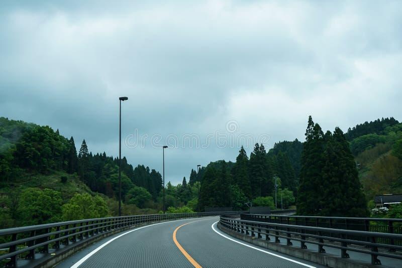 Na wyginającej się wycieczce samochodowej po padać przez miejscowy zieleni scenicznego hig obrazy royalty free