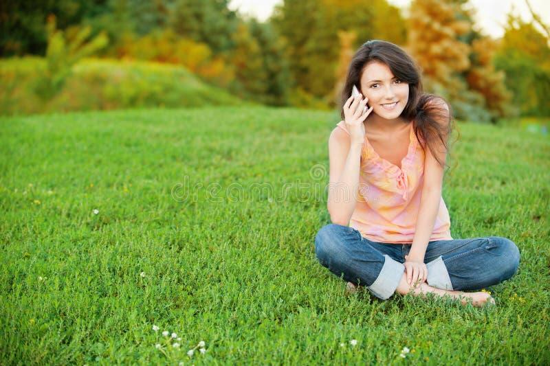 Na zielonym gazonie kobiety obsiadanie fotografia stock