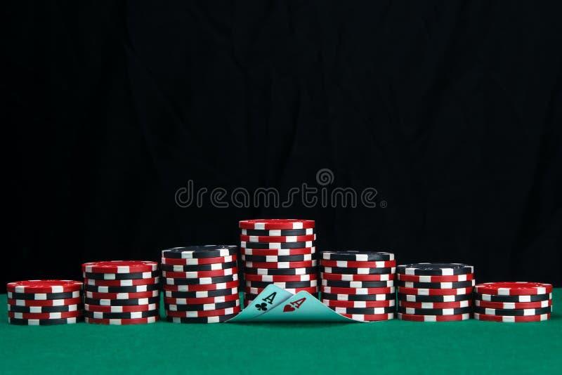 Na zielonym płótnie hazardu stół, secie układy scaleni dla bawić się w kasynie i dwa as na czarnym tle, fotografia royalty free