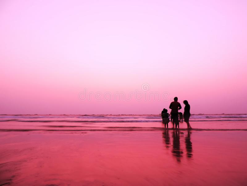 Na zonsondergangbeeld van een strand met zachte roze purpere hemelkleur samen met silhouet van een gelukkige familie met vrienden stock afbeeldingen