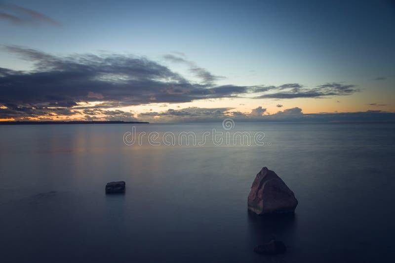 Na zonsondergangschemer over steenachtig zeegezicht royalty-vrije stock fotografie