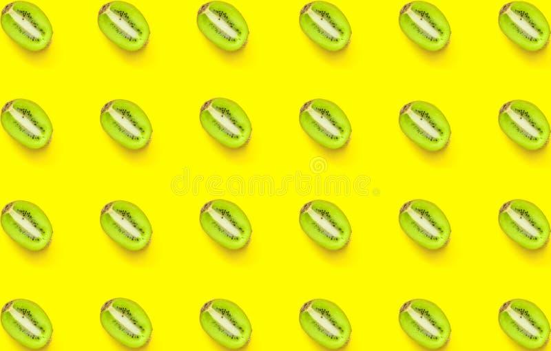 Naadloos patroon van rijpe sappige gehalveerde kiwi op gele achtergrond De creatieve Minimalistische Vlakte lag De gezonde voedin stock foto's