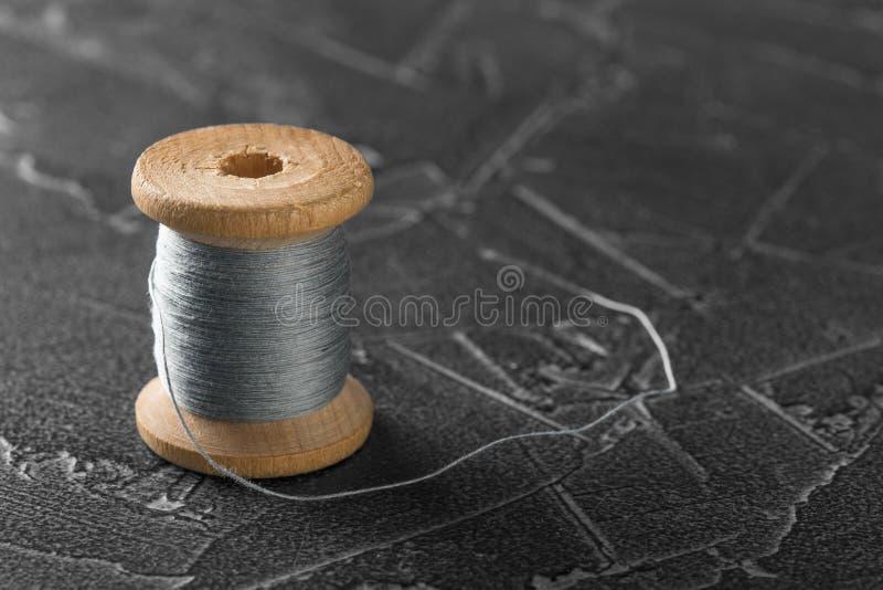 Naaiende draad op een oude houten spoel stock afbeeldingen