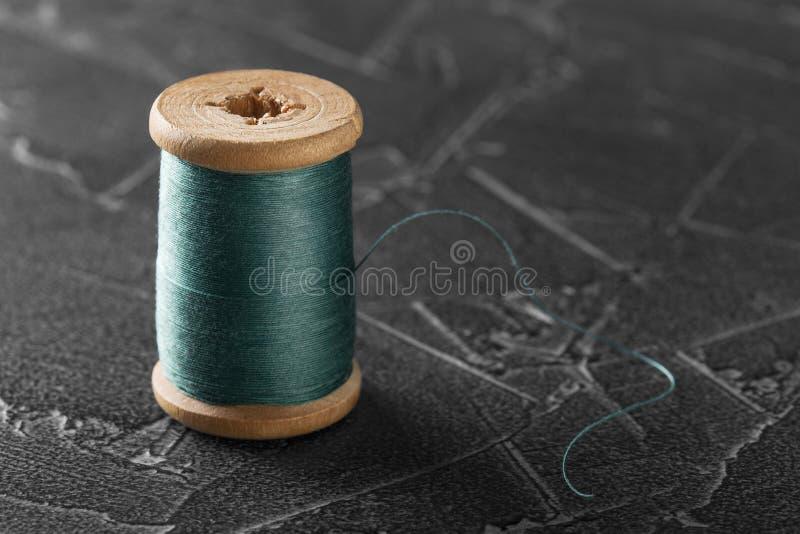Naaiende draad op een oude houten spoel stock foto