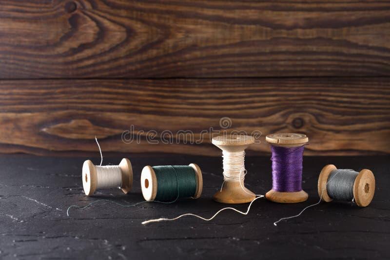 Naaiende draad op rollen, stof, naalden voor het naaien op houten achtergrond Reeks voor het maken van producten, het breien, hob stock foto