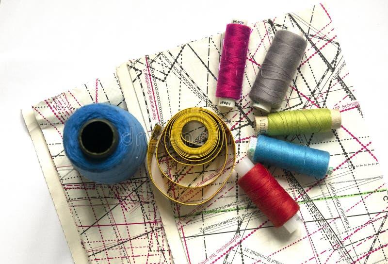 Naaiende levering op een witte houten lijst: naaiende draad, schaar, een grote spoel van draad, stukken van doek, naalden, centim royalty-vrije stock afbeeldingen