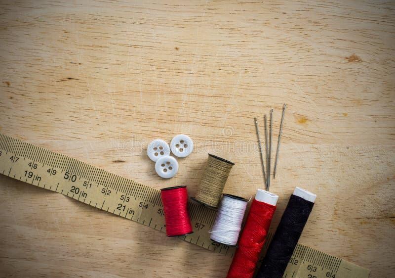 Naaiende uitrusting met draad en naalden op de houten achtergrond stock afbeeldingen
