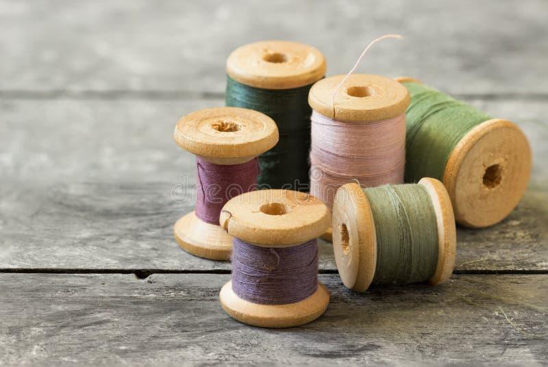 Naaiende uitrusting Spoelen van gekleurde draad op oude houten lijst stock fotografie