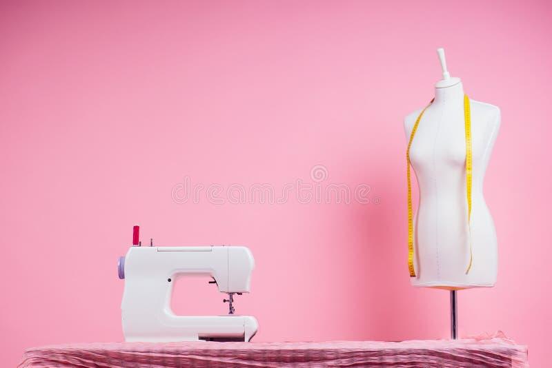 Naaigoed, naaimachine en maniken in roze achtergrond van studio naadlijnsjabloon kleermaker stock fotografie