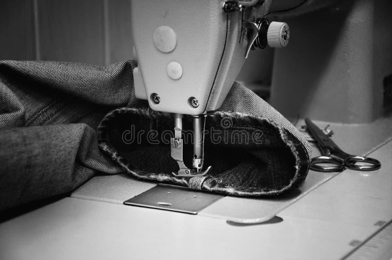 Naaimachine en jeans in het naaien van workshop zwart-wit royalty-vrije stock afbeeldingen
