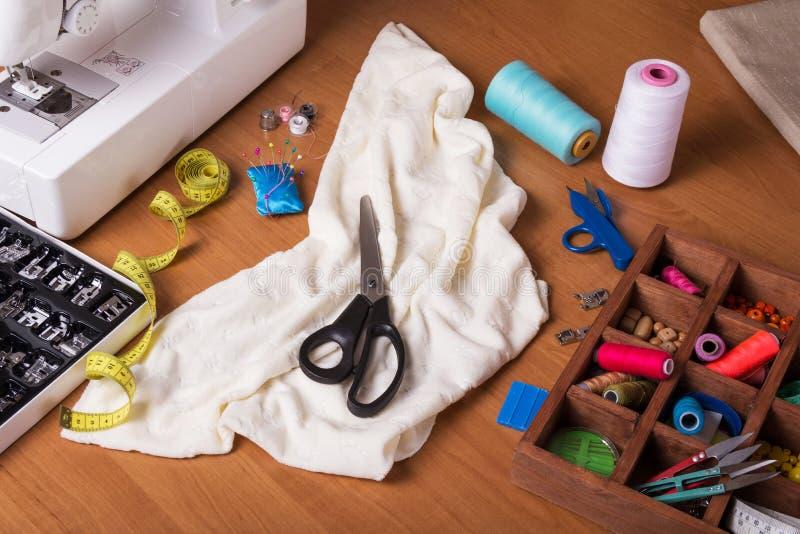 Naaimachine, houten vakje met het naaien van toebehoren, gesneden stof en schaar op lijst royalty-vrije stock fotografie