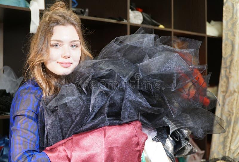 Naaister, meer costumier of verkoper die een bos van kleding houden Portret van vrouw in studio royalty-vrije stock afbeelding