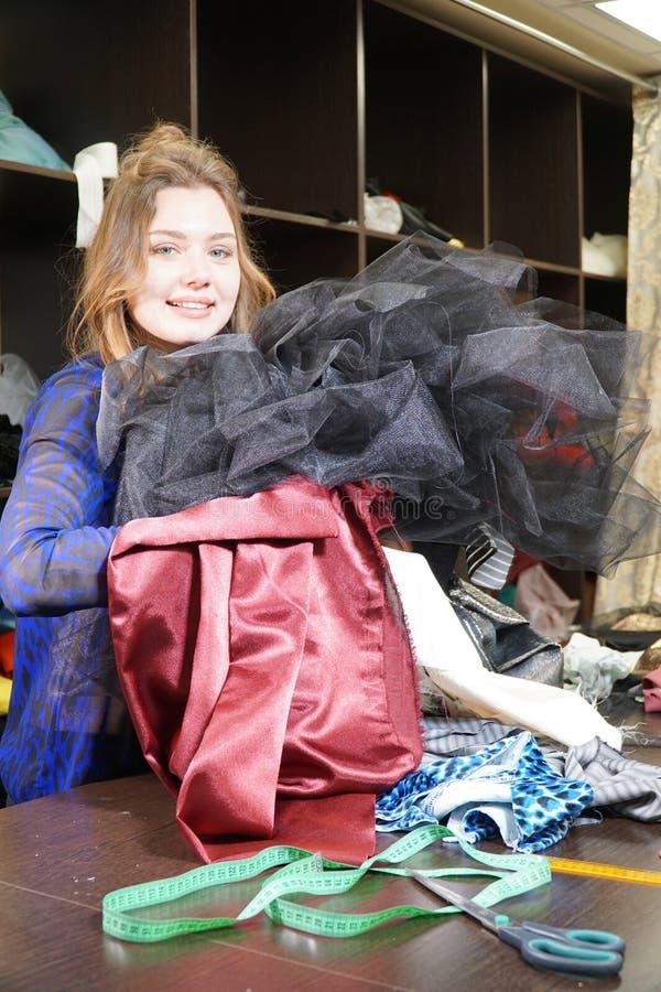 Naaister, meer costumier of verkoper die een bos van kleding houden Portret van vrouw in studio royalty-vrije stock foto's