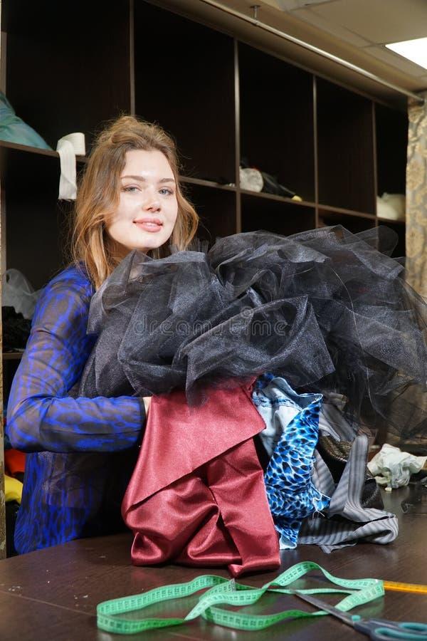 Naaister, meer costumier of verkoper die een bos van kleding houden Portret van vrouw in studio stock foto