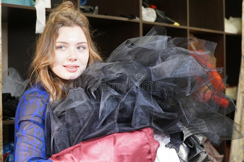 Naaister, meer costumier of verkoper die een bos van kleding houden Portret van vrouw in studio stock afbeeldingen