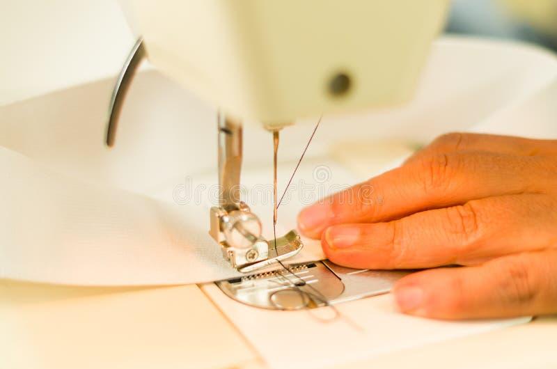 Naaisterbaan, handen die met een naaimachine naaien Witte stof en donkere draad stock foto