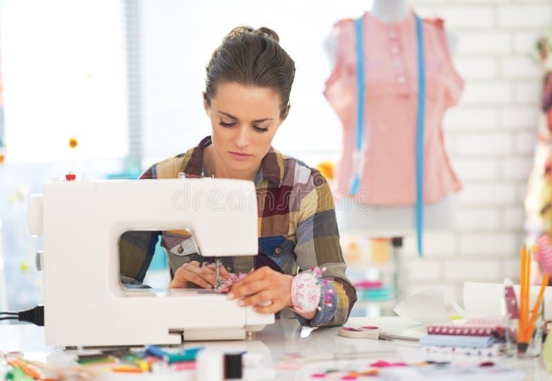Naaistervrouw die met naaimachine werken stock afbeeldingen