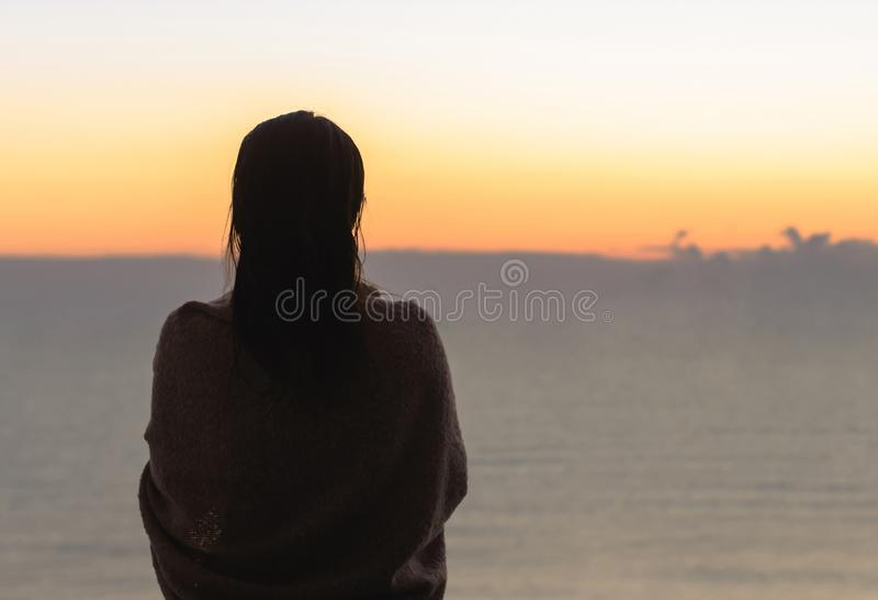 Naakt mooi wijfje met nat die haar in een deken met kop die van koffie wordt verpakt op het glasbalkon zich vroege ochtend bij su royalty-vrije stock afbeeldingen