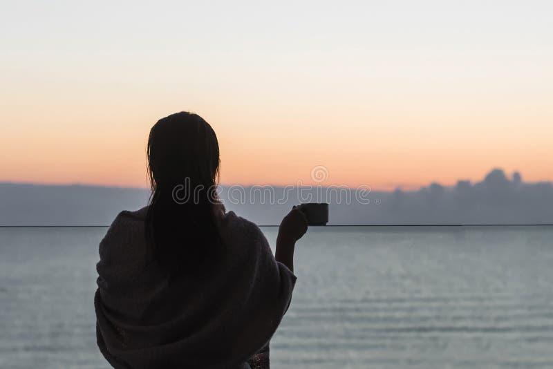 Naakt mooi wijfje met nat die haar in een deken met kop die van koffie wordt verpakt op het glasbalkon zich vroege ochtend bij su royalty-vrije stock fotografie