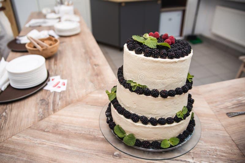 Naakte die huwelijkscake met rode bessen wordt verfraaid en het bestrooien van suikerglazuursuiker stock foto's