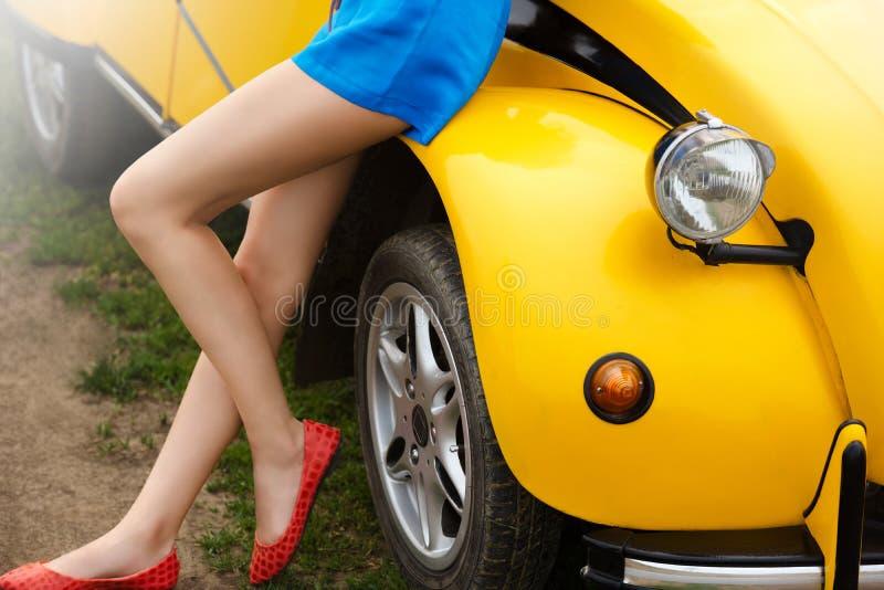 Naakte en sexy benen van een meisjeszitting op een retro gele auto in de zomer stock foto