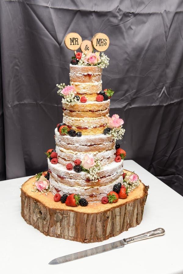 Naakte huwelijkscake met verse bessen, fruit en bloemen stock foto's