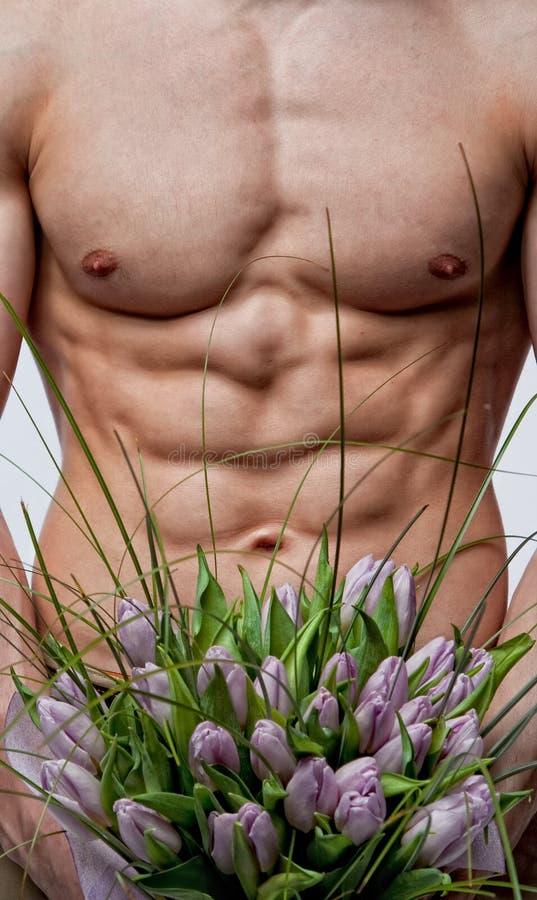 Naakte mens met boeket van tulpen royalty-vrije stock afbeeldingen