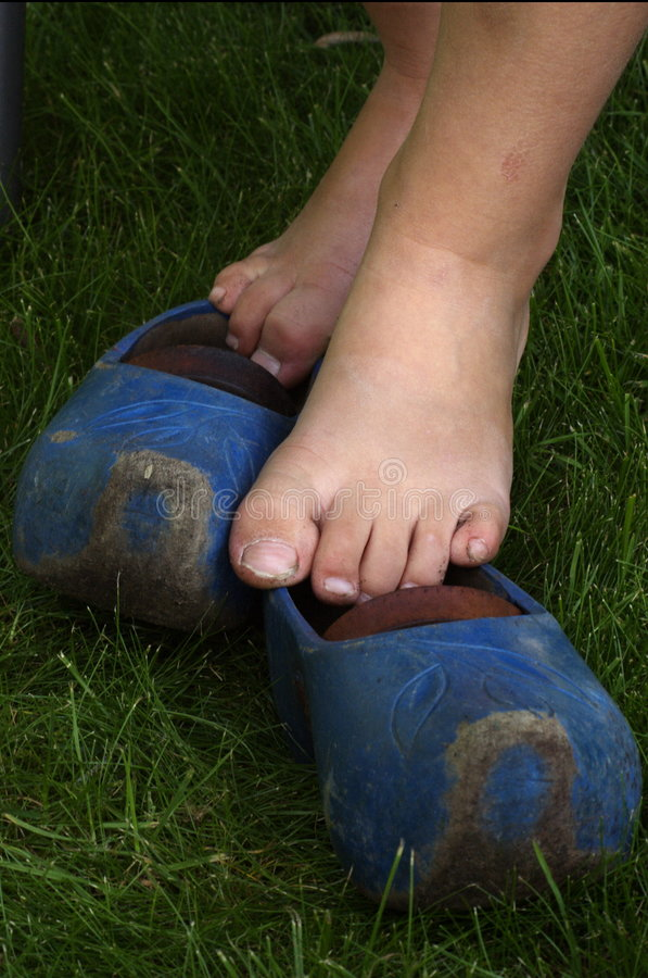 Naakte voeten op blauwe houten schoenen stock afbeelding