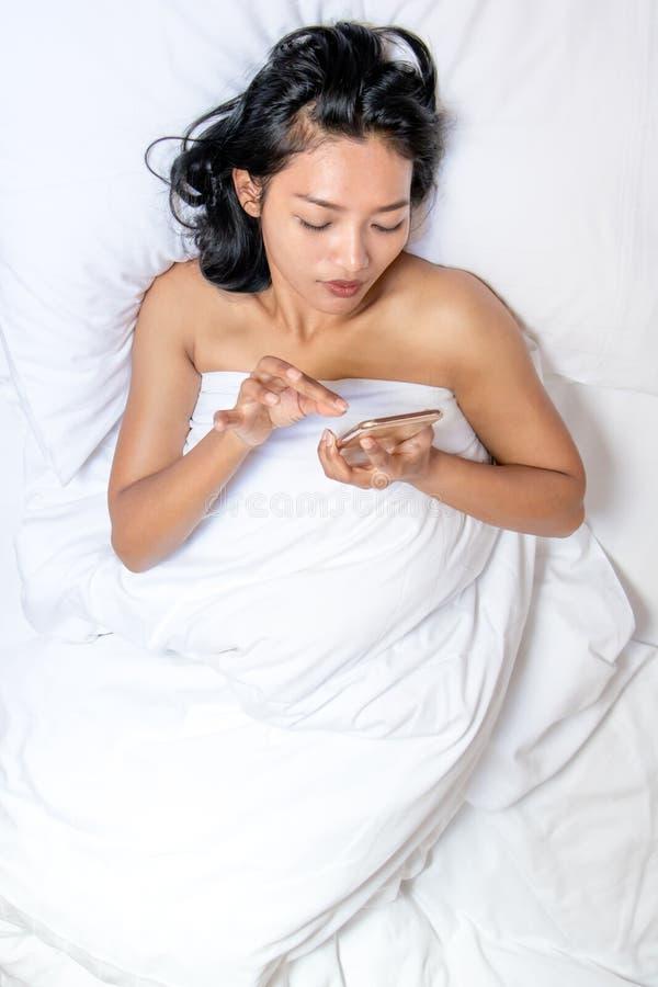 Naakte vrouw die onder een witte deken liggen royalty-vrije stock afbeelding