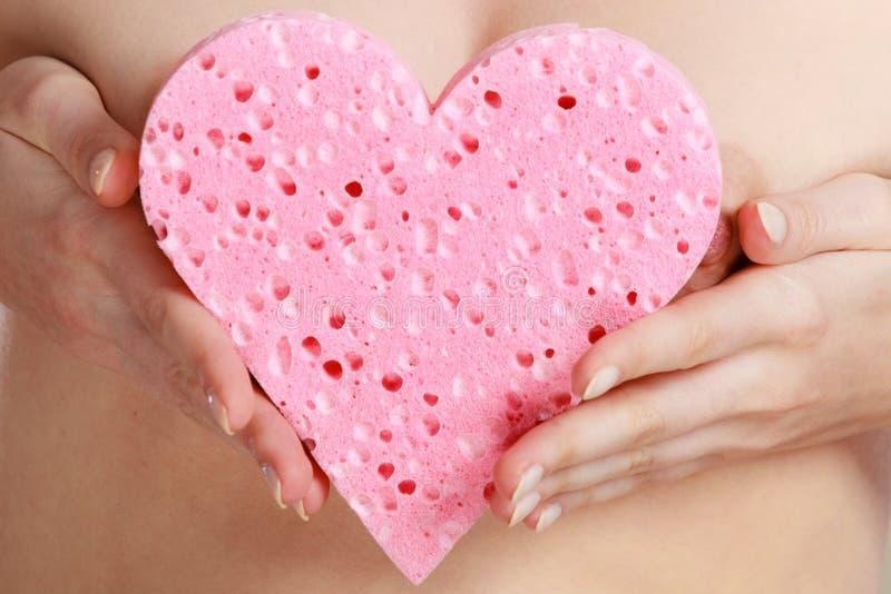 Naakte vrouw die roze hartspons in handen houden royalty-vrije stock afbeelding