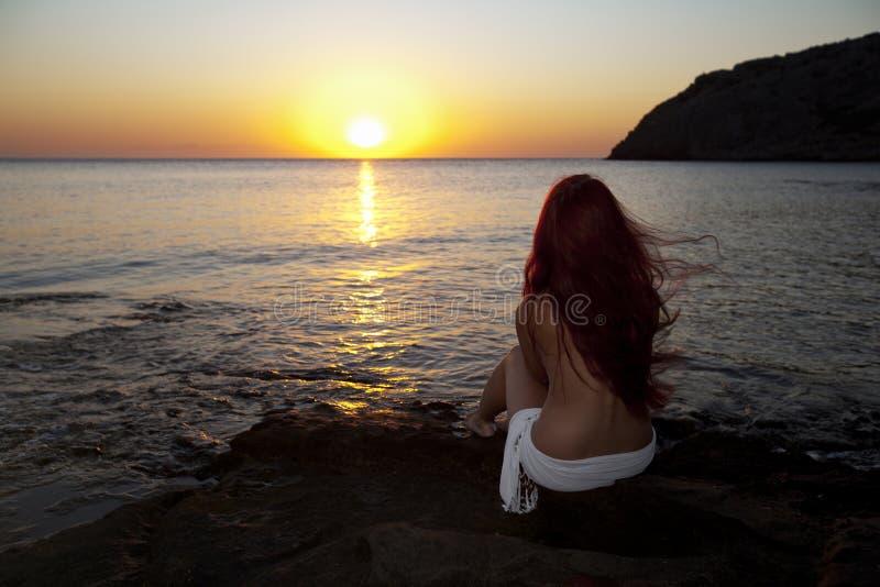 Naakte vrouw het letten op zonsopgang royalty-vrije stock foto