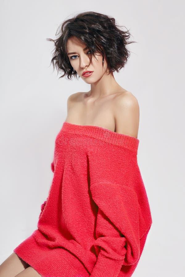 Naakte vrouw met kort haar Meisje het stellen in een rode sweater op een witte achtergrond Perfecte schone huid, Naakt lichaam va stock fotografie