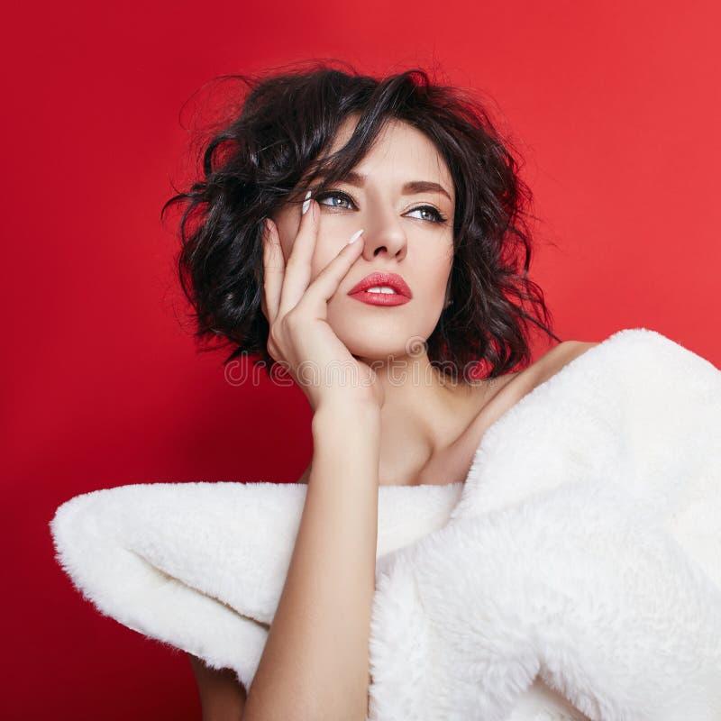 Naakte vrouw met kort haar Meisje het stellen in een wit jasje op een rode achtergrond Perfecte schone huid, Naakt lichaam van royalty-vrije stock afbeeldingen